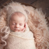 baby boy posed in newborn prop