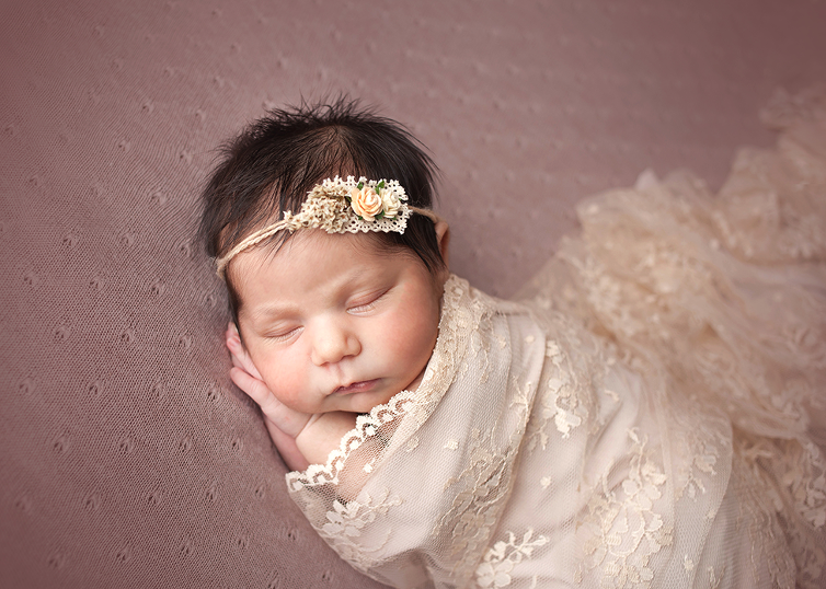 newborn girl posed session in wrap and halo in newborn prop