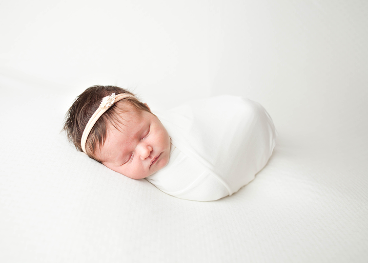 studio baby girl newborn session in lace romper tieback