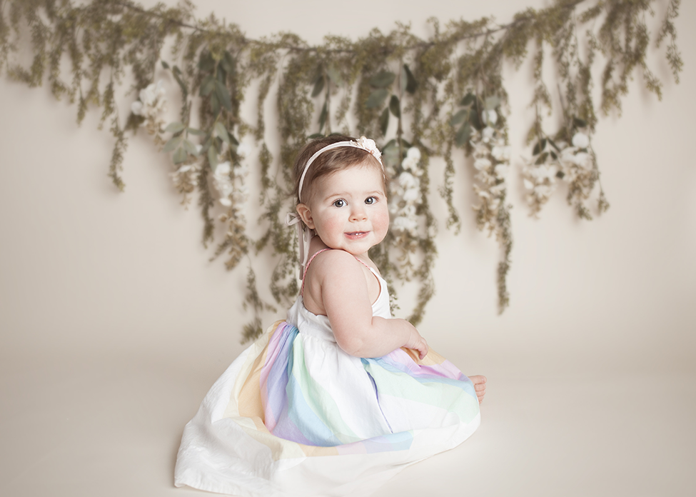 cake smash session girl in cleveland, Ohio by Chelsey Hill Photography blush cake unicorn dress bohemian set with flowers