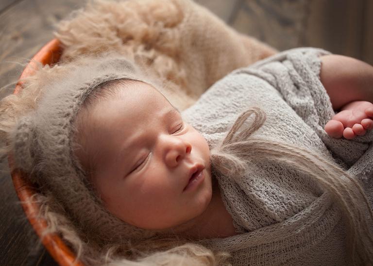 closeup of baby boy in bonnet in bowl