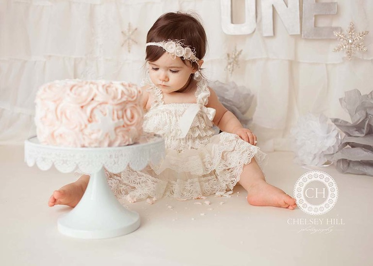 toddler girl cake smash session of lace dress and pink cake