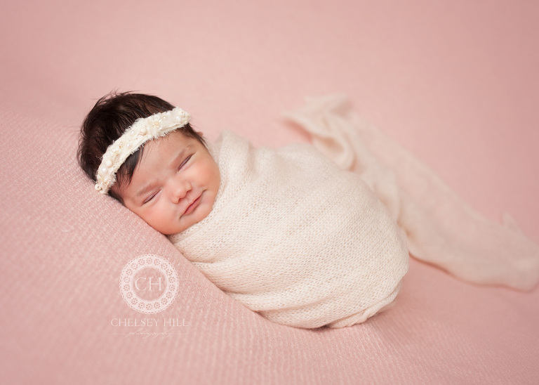 akron newborn photographer posed baby girl in pink swaddle wrap