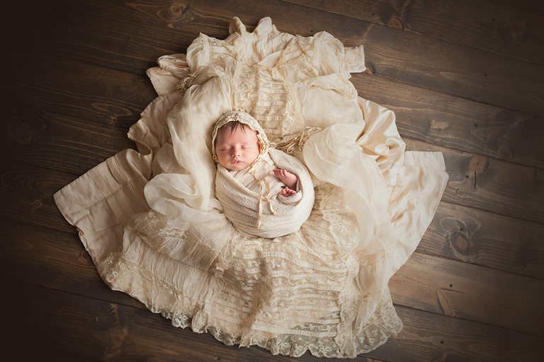 newborn boy posing on christening outfit