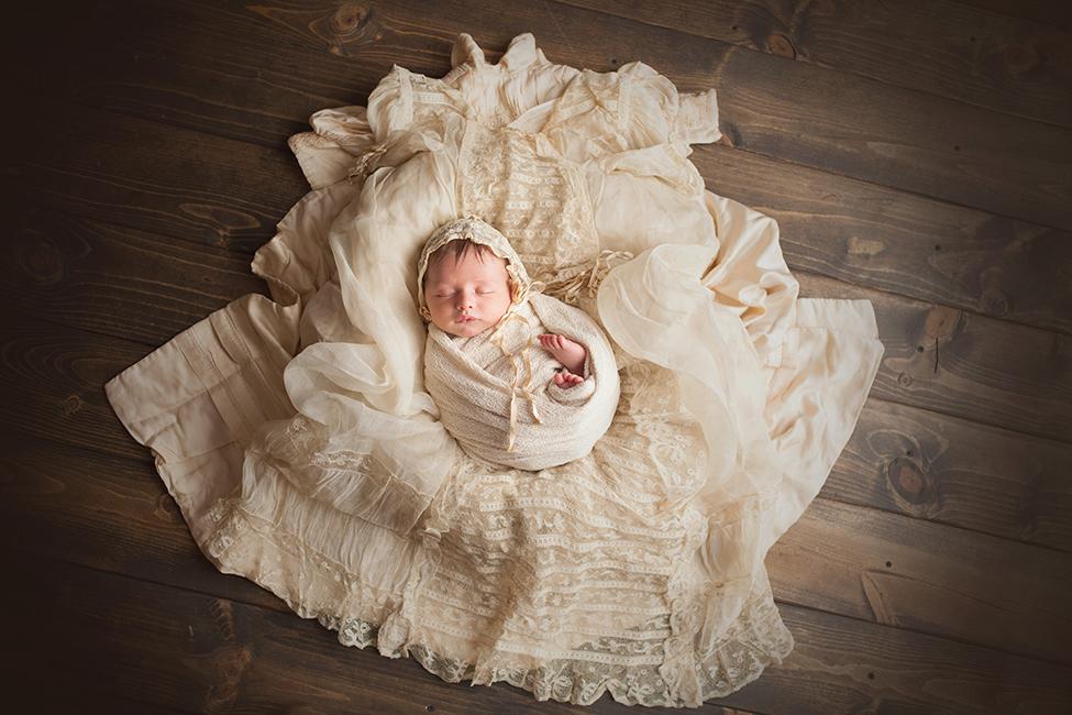 newborn boy posing on christening outfit