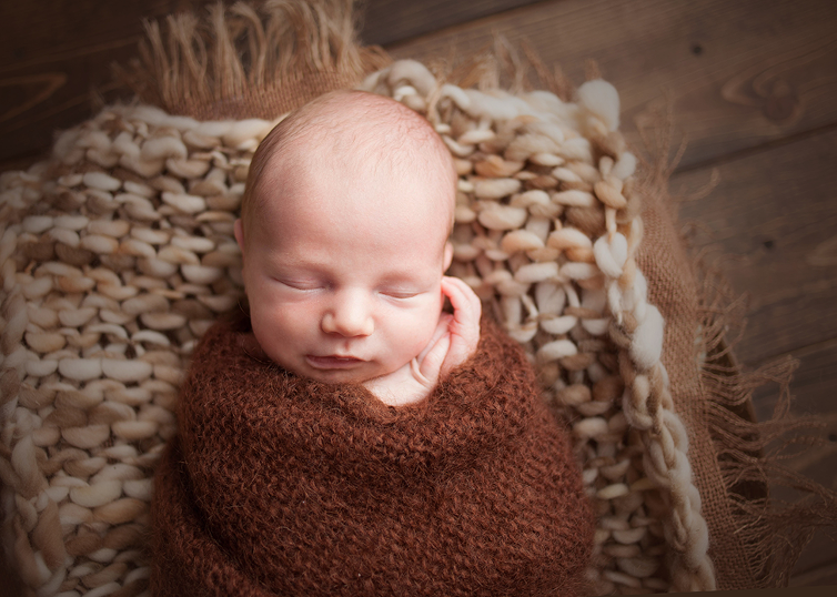 Cleveland newborn photographer posing baby in swaddle wrap