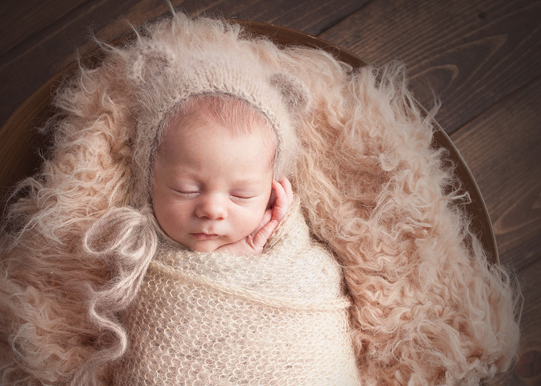 baby boy posed in newborn prop