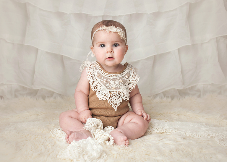6 month milestone portrait session baby girl lace romper on fur rug